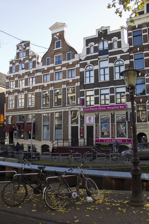 """Klassikaline läbilõige Amsterdamist. Jalgrattad, kanal, ilusad hooned ning majadel sildid märksõnadega """"Live Porno Show"""", """"Strip Club"""" jne"""